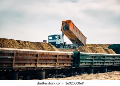 Loading railway wagons with stone, a tractor loads wagons with stone, transporting rubble on a railway