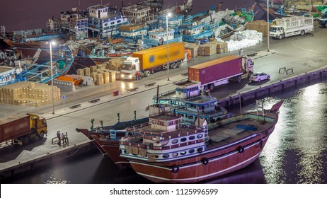 Loading a ship in Port Said night timelapse in Dubai, Deira creek, UAE. Aerial top view from above with many old boats and street lights