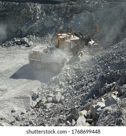Loading stones, dump truck and excavator in a cloud of stone dust while working in a slate quarry, square image.