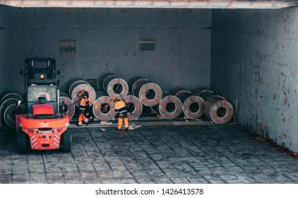Loading and unloading process of steel coils in cargo port. Carry steel coils. View on procces into cargo hold. Copy space. Background. Living coral lifter. Living coral clothes on stevedors.