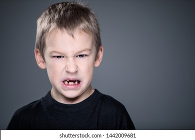 Loads of aggression in a little boy - education concept hinting behavioral problems in young children (shallow DOF) - little boy with hands clenched into fists about to punch someone