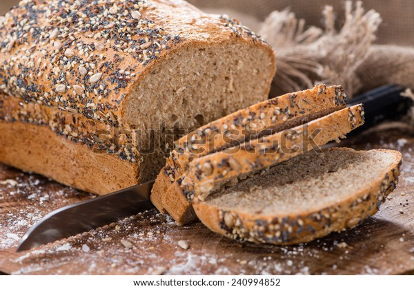 Loaf of bread (fresh baked) on rustic wooden background