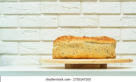 A loaf of bread, good-looking, big baked at home. Bread with seeds on a wooden board on a white background