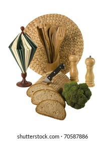 Loaf of bread with knife, broccoli,pepper and salt, napkin paper, wooden cooking tools and rattan placement - all isolated over white background
