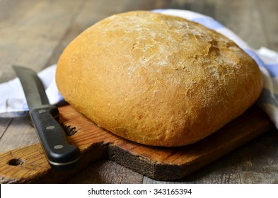 Loaf of bread with knife on rustic background.