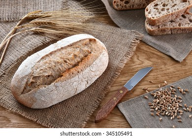 A loaf of bread with a knife and some barley ears a wooden background