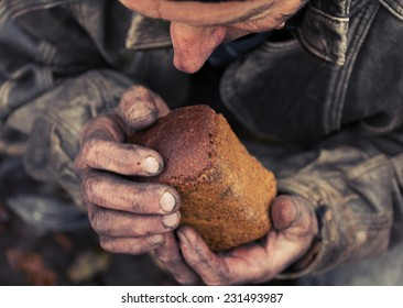 A loaf of bread in an old mans hands
