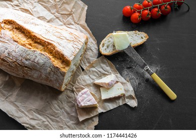 Loaf of Bread on Craft Paper and a Black Table with Tomatoes, cheese, Butter and a Knife