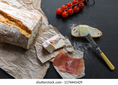 Loaf of Bread on Craft Paper and a Black Table with Tomatoes, cheese, Ham, Butter and a Knife