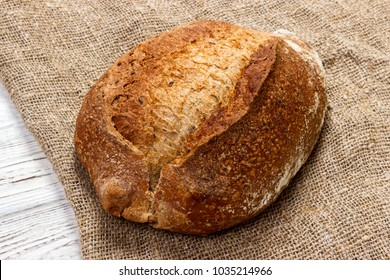 loaf of bread on wooden background, food closeup.