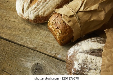 A loaf of Bread packed in paper on wooden table.