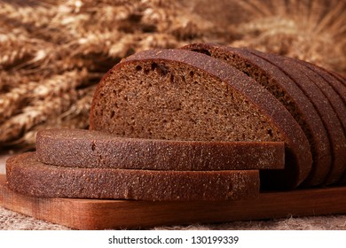 Loaf of bread and rye ears still life on rustic background