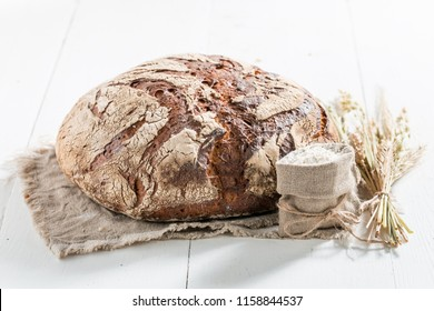Loaf of bread with several grains on linen cloth