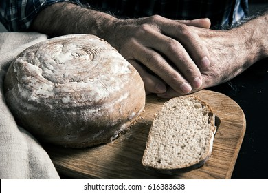 Loaf of bread with slice cut on the board. Hands of elderly man at the table next to bread as a symbol of hard work and agriculture.