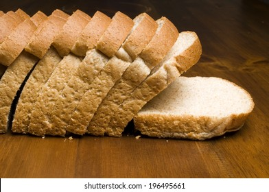 A loaf of bread sliced with the end lying on a table.