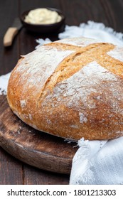 Loaf of Classic Boule bread on dark wooden board with a white cloth, vertical