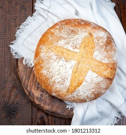 Loaf of Classic Boule bread on dark wooden board with a white cloth, top view, square format