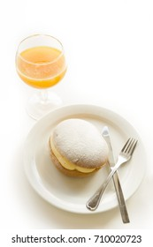 Loaf with custard cream and glass of orange juice served for breakfast isolated on white.