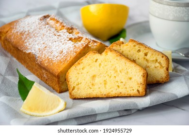 Loaf of gluten free lemon cake with sugar powder, pieces of lemon and cup on kitchen towel on marble table. Close up slice of citrus pie by classic recipe. Healthy nutrition, homemade vegan dessert.