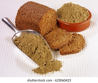 LOAF OF HEMP BREAD WITH HEMP FLOUR IN BOWL AND SCOOP,ON WHITE TABLETOP