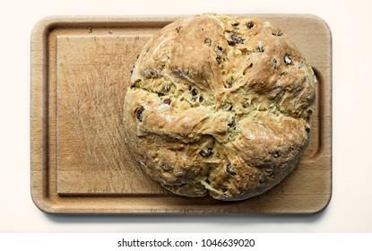 A loaf of homemade Irish soda bread with raisins on a wood board.