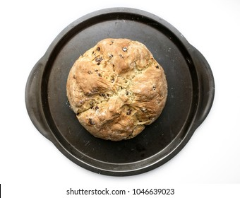 A loaf of homemade Irish soda bread with raisins on a metal baking pan.