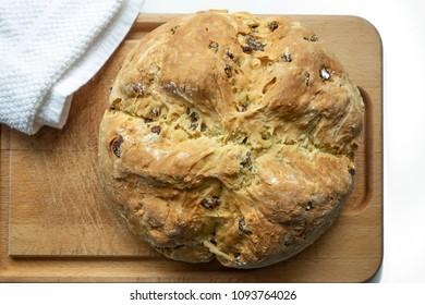 A loaf of homemade Irish soda bread with raisins on a wooden cutting board