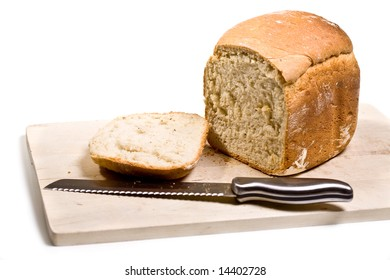 Loaf of homemade white bread on cutting board - isolated on white background