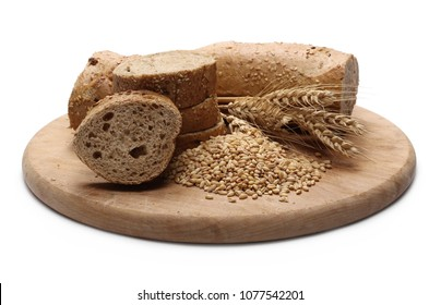 Loaf of integral bread with sesame, ears of wheat, grains and slices on wooden cutting board isolated on white background