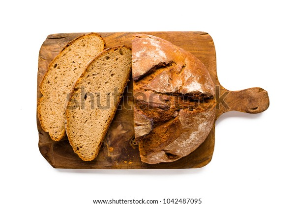 Loaf of rustic german bread, partly sliced, on wooden breadboard, isolated on white background, view from above, close-up.