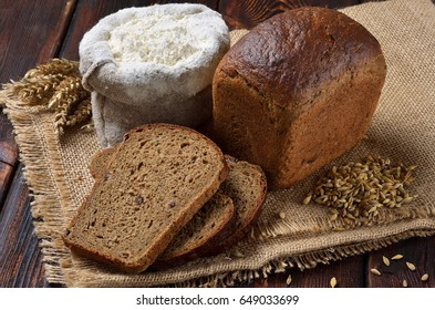 A loaf of rye bread with slices on sackcloth background