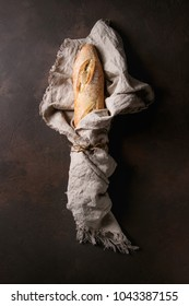 Loaf of sliced fresh baked artisan baguette bread wrapped in linen cloth over dark brown texture background. Top view, copy space.