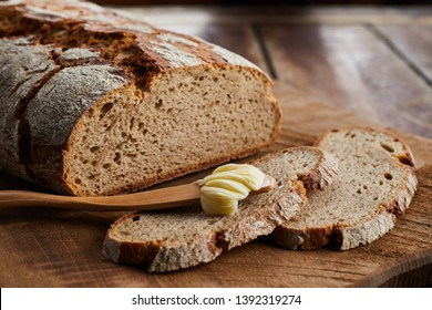 Loaf of sliced rye bread with wooden butter spreader with scoop of butter on an old board viewed low angle on a table with copy space