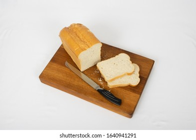 Loaf and slices of white bread on cutting board, with knife, on white background