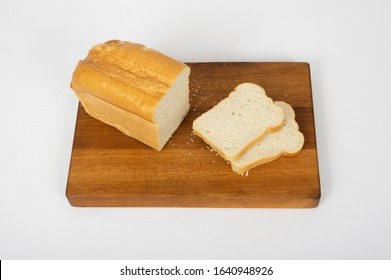 Loaf and slices of white bread on cutting board, on white background