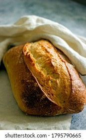Loaf of sourdough craft bread on a dark background close-up, vertical background, copy space