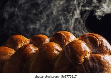 A loaf of steaming hot challah bread, fresh from the oven