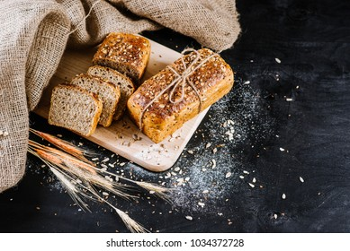 Loafes of fresh baked bread on the black wooden background. Bread rye spikelets on an black board