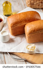 Loafs of white brick shaped bread with butter and coffee on the wooden board