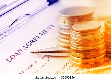 Loan agreement with a blue ballpoint pen and stacks of coins. A loan agreement is a contract between a borrower and a lender which regulates the mutual promises made by each party. Financial concept.