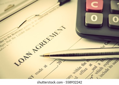 Loan agreement on a clipboard. Loan agreement is a contract which regurates mutual promises made by a borrower and a lender. Types of loan agreements i.e. facilities agreements, revolvers, term loans.