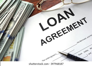 Loan agreement on a table and dollars.