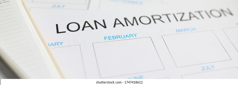 Loan amortization paper plan lying at worktable ready to be filled close-up
