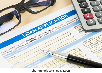 Loan application form with calculator, glasses, and pen