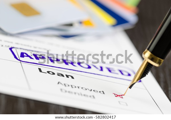 Loan form close up, fountain pen and approved stamped on a document. Soft focus.