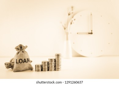 Loan or lending cash to buy asset concept : Loan bags and stacks of rising coins, fiat money on a table, depicts a borrower or debtor always borrow money from lender in higher amount and never payback