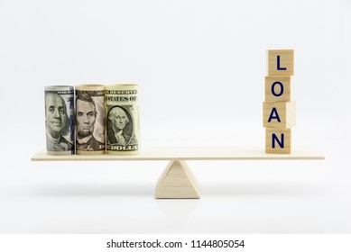 Loan or lending cash, financial concept : Wood blocks with a word LOAN and US USD dollar bills on a seesaw or basic balance scale, depicts a borrower always borrow money from lender in higher amount