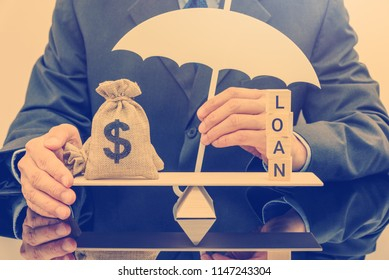 Loan protection insurance / financial support concept : Businessman holds umbrella guards dollar money bags on a simple balance scale, depicts protection policy that protects the insurer from default