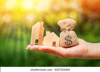Loan or save for buy a house and real estate concept, Woman hand holding money bags and a model home in the public park.