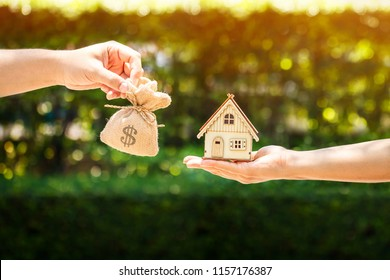 Loan or save for buy a house and real estate concept, Man and women hand holding money bags and a home model put together in the public park.